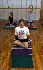 Yoga students Holly Krebs, left, Phil Schrodt, center, and Steven Maynard-Moody stretch before class.
