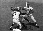 San Francisco pitcher Juan Marichal (27) swings a bat at Dodgers catcher John Roseboro as Dodgers pitcher Sandy Koufax, right, tries to break up the fight. The melee which started when Marichal apparently felt Roseboro had returned a pitch too close to Marichal's head came in the third inning of the game on Aug. 22, 1965, in San Francisco.