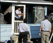 Investigators from the Mississippi Crime Lab, from left, Steve Chancellor, Jackie Johnson and Jon Byrd, examine bullet holes at a house in Friars Point, Miss. The house was the site of a bloody shootout Sunday between police and Patrick Harper, a suspect in a Friday shooting. Five law enforcement officers were wounded.