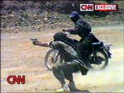 Trainees take part in mock terror attacks in this undated videotape made by al-Qaida and aired Wednesday by CNN. Dozens of men wearing battle uniforms, combat helmets and scarves on their faces blew up buildings and bridges, took hostages at gunpoint and carried out assassinations in the footage.