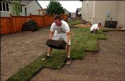 Quinton Galtney, left, lays a roll of sod as co-worker Brian Crisp tucks in the edges of a new lawn at 1108 Langston Court.