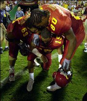 Iowa State quarterback Seneca Wallace (15) is consoled by teammates Dwayne Johnson (69) and Lance Young. The Cyclones fell to Florida State, 38-31, on Saturday in Kansas City, Mo.