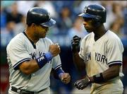 Alfonso Soriano, right, is congratulated by Raul Mondesi after slamming a two-run homer in the second inning of Friday's game. The Yankees won, 9-7.
