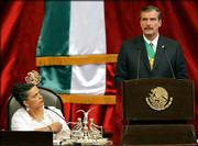 Mexican President Vicente Fox gives his state-of-the-nation address at a joint session of Mexico's Congress. Congressional President Beatriz Paredes, from the opposition PRI party, looked on during the speech Sunday. Fox overthrew Mexico's entrenched political elite two years ago, but Mexicans are growing increasingly impatient with the pace of his reforms.