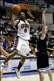 Kansas University product Paul Pierce, left, of the United States, makes a pass over New Zealand's Mark Dickel. The U.S. pounded New Zealand in the World Basketball Championships on Tuesday in Indianapolis.