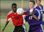 Lawrence High's Ibrahim bah, left, holds off Topeka West's Tyson Revell. The Lions fell, 4-1, on Tuesday at the Youth Sports Inc. fields..