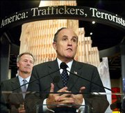"Standing in front of a scene of the World Trade Center devastation, former New York City Mayor Rudy Giuliani helps launch a new exhibit at the Drug Enforcement Administration Headquarters in Arlington, Va., as DEA Director Asa Hutchinson listens at left. The display, called ""Target America,"" draws connections between terrorism and drug trafficking."