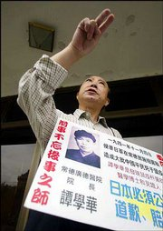 Tan Jialin, 65, holds a placard that describes how his father, H.H. Tang, gathered medical evidence of Japanese biological warfare early in World War II. Tan and other victims protested Tuesday in Beijing and said they would appeal a Japanese court's decision not to grant them compensation.