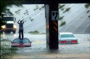 A man reacts after driving his car into high water underneath a railroad crossing overpass in San Antonio. The man drove in despite another car, right, already being stuck in the high water on Saturday. Tropical Storm Fay is moving across south Texas, and rains Saturday morning in San Antonio ranged from 2 to 4 inches.