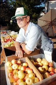 Floyd Ott, who lives south of Eudora, rests on his selection of apples at the Lawrence Farmers Market. Ott was among the area growers selling their goods Saturday at the market, 10th and Vermont streets.