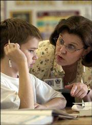 Quail Run school fifth-grader Brain Gauch, left, gets advice from his teacher, Christine Valcich, while working on some math exercises. Gauch and his classmates were working on graphing lessons Tuesday. Quail Run achieved the state's standard of excellence in math and reading.