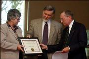 Kansas University librarian William Crowe, center, is presented the Gretchen and Gene A. Budig Distinguished Librarian Award by KU Dean of Libraries Stella Bentley, left, and Gene Budig, a former KU chancellor. Crowe became the first recipient of the endowed award Wednesday at Spencer Research Library.