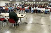 More than 700 people wait for the beginning of the U.S. Army Corps of Engineers' public hearing on the South Lawrence Trafficway. Army Col. Dan Curtis, foreground, was in charge of the meeting at the Douglas County 4-H Fairgrounds.