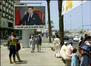"Residents and tourists walk beneath a banner of King Mohamed VI on Tangier&squot;s seafront Royal Armed Forces Boulevard. The 38-year-old monarch gave his third annual speech from the throne this summer in Tangier, reversing more than three decades of official neglect of the legendary Moroccan city. The banner reads, in Arabic, ""Happy anniversary and long life."""