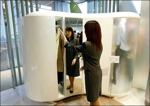 Demonstrator Maki Kakuta Opens A Prototype Of A High Tech Closet Developed  By Matsushita Electric Industrial Co. The Automated Closet Can Pick Out  Clothes ...
