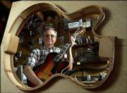 AP Photos Nelson Palen of Beloit, is seen through a template while holding one of the archtop jazz guitars he made in his basement workshop.