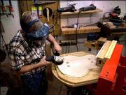 Palen grinds down a piece of wood to be used for the back of a guitar. He uses caliper to determine the back's thickness. During the past three years, Palen has earned the respect of jazz guitarists throughout the world, including famed jazz guitarist and singer George Benson, who bought one of Palen's creations.