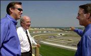 Developer Hugh Zimmer, center, looks over Kansas Speedway and the Village West tourism district with Bill Crandall, left, vice president for Zimmer Management, and speedway president Jeff Boerger in Kansas City, Kan. The speedway has helped bring unprecedented development to Wyandotte County.