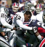 Oakland's Anthony Dorsett (33) loses his helmet as he tackles Buffalo's Travis Henry (20). The Raiders beat the Bills, 49-31, on Sunday in Orchard Park, N.Y.