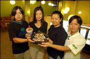 The Pochi Tea Station, 125 E. 10th St., is introducing Lawrence customers to bubble tea. The restaurant is run by family members from left, Bao Quan Cai, 27, Ervana Tjhai, 17, Erlinda Tjhai, 24, and Agustiwan Tjhai, 20. The restaurant, which opened about two weeks ago, serves drinks and Indonesian dishes.