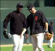 San Francisco's Barry Bonds, left, and Rich Aurilia chat in the outfield at Pac Bell Park on Friday in San Francisco. The Giants will play the St. Louis Cardinals in Game 3 of the NLCS tonight.