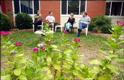 Workers at the United Way building Daniel Pennington, left, David Morrissey, Jerilyn Smith and Rich Minder, enjoy a break in the courtyard.