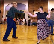Gordon Dryer, Blue Springs, Mo., swings his partner, Beverly Ruiz, Bloomington, Ind., at the Lawrence Barn Dance Assn.'s 20th anniversary celebration at Woodlawn School.
