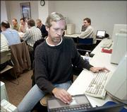 Doug Ecklund works on the computer network at the Barrington Career Center while unemployed clients exchange information during a networking session in Barrington, Ill. Ecklund, who has been unemployed for nearly a year, volunteers at the career center and helped begin its computer network that allows clients to post rm