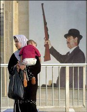 An Iraqi woman carrying her child walks in front of a poster of President Saddam Hussein holding a rifle Saturday in Baghdad.