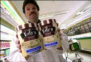 Steve Luongo, dairy manager of Super Fresh supermarket in Northfield, N.J., holds the original half-gallon size ice cream container, at left, and the new 1.75-quart container. Edy's is among the brands changing to a smaller size container to effectively deal with increasing costs without increasing the price of their product.