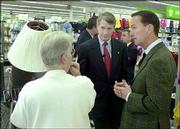 Kmart Corp. president Julian Day, center, and Chief Executive James Adamson, right, meet with a customer at the company's prototype store in White Lake Township, Mich. Adamson says the company plans to emerge from bankruptcy as early as the first half of 2003.