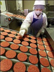 A worker watches the hamburger patties moving on the conveyer belt at McDonald's plant in Chiba, east of Tokyo. McDonald's Corp. reported an 11 percent drop in earnings Tuesday, its seventh decline in the last eight quarters.