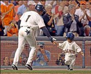 San Francisco's Kenny Lofton slaps hands with bat boy Darren Baker, 3, son of Giants manager Dusty Baker, after Lofton scored during the NL division series against Atlanta in San Francisco. The sons of Barry Bonds, Jeff Kent and Shawon Dunston also hang out with the Giants players.