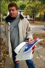 Rich Minder collects political signs strewn across his yard in the 1500 block of Rhode Island Street. Lawrence Police said they found sporadic yard sign damage on Tuesday, apparently targeted toward Democratic campaign materials.