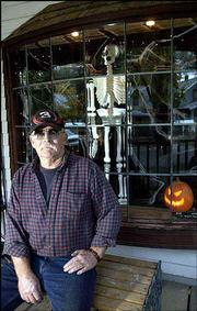 The highlight of Ed Boyle's house at 310 Elm St. is his spooky front window complete with a hanging skeleton.