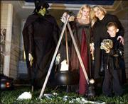 Niki Osburn, middle, and her family Kirsten, 13, and Ryan, 6, are sure to spook their share of trick-or-treaters this Halloween. Pictured at left is their life-size witch with her cauldron.