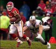 Kansas City running back Priest Holmes (31) avoids Oakland's Trace Armstrong. Holmes had 184 yards total offense as the Chiefs knocked off the Raiders, 20-10, on Sunday at Kansas City, Mo.