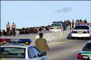 Police detain illegal immigrants on the Rickenbacker Causeway leading from Miami to Key Biscayne, Fla. After their 50-foot wooden freighter ran aground off Virginia Key Tuesday, more than 200 illegal Haitian immigrants jumped overboard,waded ashore and rushed onto the highway, causing the six-lane Rickenbacker to be shut down.