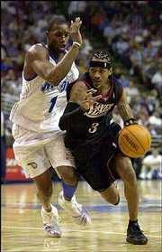 Philadelphia guard Allen Iverson, right, drives to the basket past Orlando's Tracy McGrady (1) in the second quarter of their game. The Magic won, 95-88, Tuesday in Orlando, Fla.