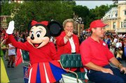 Jackie Autry, center, accompanied by Minnie Mouse, points to cheering fans. The Angels once owned by Autry's late husband, Gene Autry were honored during a parade Tuesday in Disneyland.
