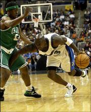Washington's Michael Jordan (23) plows past Boston's Shammond Williams during the Wizards' 114-69 win Thursday night. A night after missing two free throws and a breakaway dunk in the fourth quarter of a loss in Toronto, Jordan scored 21 points in 21 minutes against the Celtics.