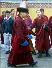 A young Mongolian monk, right, seeks blessings from a senior monk walking past at a monastery in Ulan Bator. The Dalai Lama, a Buddhist spiritual leader, today visited the Gandan monastery after arriving Monday from Japan.
