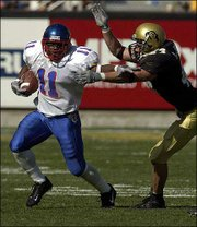 Kansas University running back Reggie Duncan, left, brushes off Colorado linebacker Joey Johnson in this 2001 file photo.