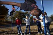 Charles Jackson, third-grader at East Heights School, foreground center, prepares to do a flip off some playground equipment during recess. Watching from left are Tyrin Thorne, fourth-grader, Holly Von Bargen, fifth-grader, and Alex Scott, fourth-grader. East Heights is one of three schools that the school board has tentatively decided to close after weighing input from a districtwide facilities study by DLR Group.