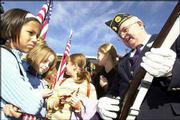 Hillcrest School fifth-grade students, from left, Mica Mendez, Catherine Morel, Ayjan Arik and Nikki Walker, get a closer look at Jerry Hanson's World War I- and World War II-era Springfield rifle at the Veterans Day ceremony at the Alford-Clarke Post 852 of the Veterans of Foreign Wars, 138 Ala. Hanson was part of Monday's 21-gun salute. He is in the honor guard at the American Legion Dorsey-Liberty Post 14 in Lawrence.