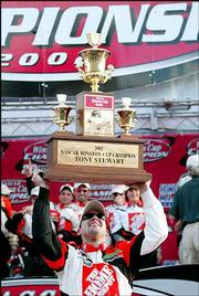 Tony Stewart hoists his championship trophy after capturing the 2002 NASCAR Winston Cup title. He sealed the victory with his 18th-place finish in the Ford 400 Sunday in Homestead, Fla.
