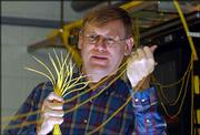 Kansas University researcher Chris Allen is among the group of KU professors who have received a patent for technology that will speed up fiber-optic networks. Allen examines fiber-optic cable this week at his laboratory on KU's West Campus.