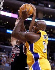 Los Angeles' Shaquille O'Neal, right, grabs a rebound from Chicago's Donyell Marshall. O'Neal made his season debut, scoring 17 points and snaring seven rebounds, and the Lakers defeated the Bulls, 86-73, Friday night in Los Angeles.