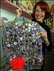 Bridgette Sesti holds a jacket covered with vintage rock music buttons at the Hullabaloo warehouse in St. Louis. The buttons are just a small sample of the memorabilia that has been collected by Hullabaloo.