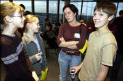Members of the Lawrence children's choir, Justine Ahle, 12, and Lindsay Gauthier, 12, at left, speak with Moscow Boys Choir member Volodya Fadin, 14, with the help of interpreter Yana Grigortchouk, a Kansas University graduate student from Petrozavodsk, Russia, center, during a choir exchange at the Lied Center. The two choirs met on Saturday, prior to the Moscow Boys Choir's performance that evening. Choir members talked with the help of interpreters and learned that they have a lot more in common than they thought they would. Later, Lawrence choir members got to listen to the Moscow Boys Choir's dress rehearsal.